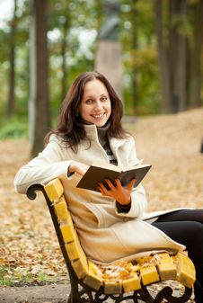 Free Young Woman Sitting On Bench In Autumn Stock Photos - 16394943