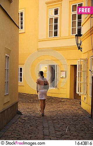 Girl walking between yellow buildings Stock Photo