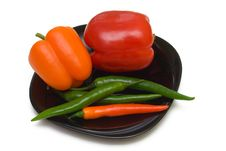 Bell And Chilli Peppers On Black Plate Stock Photo