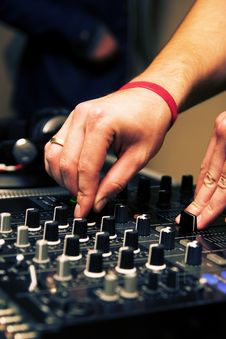 DJ Adjusting Music Level On Mixer Royalty Free Stock Images