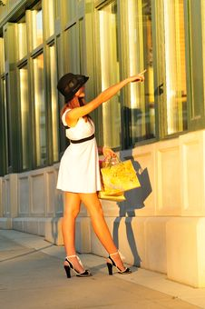 Woman Pointing At A Store Window Stock Photo