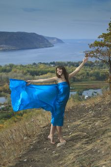 Free A Young Girl In A Blue Dress Dancing On A Mountain Stock Photo - 16469950