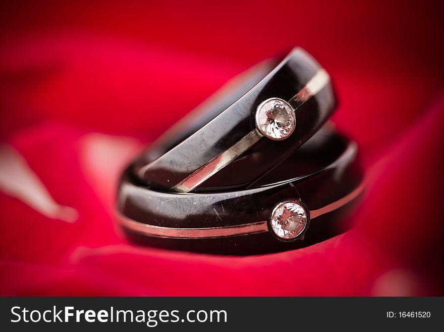 Dark Wedding Rings on Red Petals