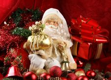 A Toy Santa Claus On A Background With Red Ribbons Royalty Free Stock Photo