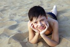 Smiling Boy Sunbathes On A Beach Royalty Free Stock Photos