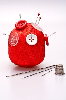 Pins In Wool Ball With Buttons Royalty Free Stock Photos