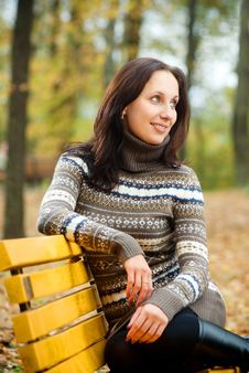 Young Woman Sitting On A Bench In Autumn Park Stock Photography