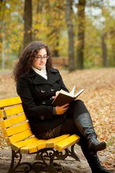 Free Young Woman Reading Book On Bench Royalty Free Stock Image - 16497756
