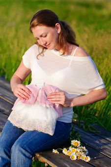 Pregnant Woman With First Cloth For Newborn Stock Photography