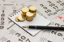 Free Sheets Of A Calendar With Coins And A Notebook Royalty Free Stock Photography - 16555067