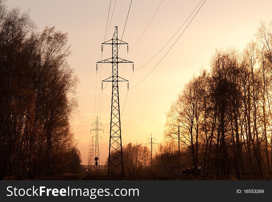 Electricity pylons and lines at sunset.