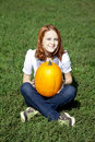 Free Women Sitting At Green Grass And Keeping Pumpkin. Royalty Free Stock Photo - 16562545