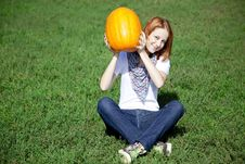 Free Women Sitting At Green Grass And Keeping Pumpkin. Royalty Free Stock Photography - 16562557