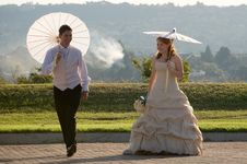 Free Bride And Groom Walking Outside In Sun With Umbrel Royalty Free Stock Photography - 16565077