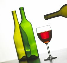 Glass Of Red Wine With Two Green Wine Bottles Stock Images