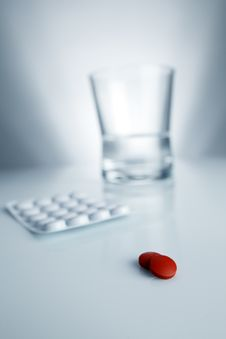 Medical Red Pill And Aspirin With Water And Glass Stock Images