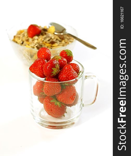 Strawberry in glass and muesli isolated on white