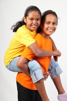 Two Young School Girls Have Fun Giving Piggy Back Stock Photos
