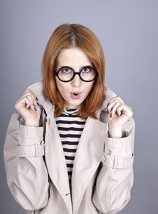 Young Red-haired Girl In Glasses And Cloak. Royalty Free Stock Photo