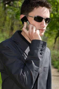 Man In Sunglasses And Jacket Talks On Cell Phone Stock Photos