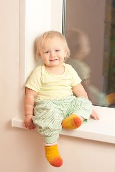 Adorable Girl Sitting On The Window Sill Stock Photos