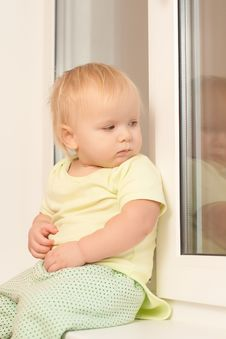 Adorable Girl Sitting On The Window Sill Royalty Free Stock Photography