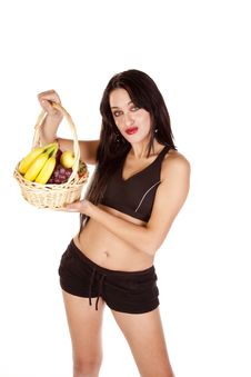 Free Woman Holding A Basket Of Fruit Looking Stock Images - 16704334