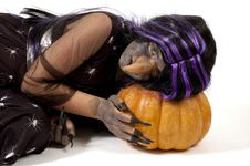 Free Girl Dressed Up As A Witch Sleeping On A Pumpkin Stock Images - 16721274