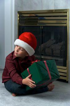 Free Boy In Santa Hat Shaking Gift Royalty Free Stock Photos - 16725028