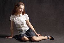 Girl Sitting On Floor In Skirt Black Background Royalty Free Stock Photo