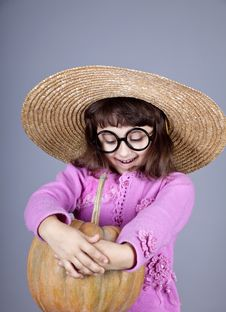 Funny Girl In Cap And Glasses Keeping Pumpkin. Royalty Free Stock Photography