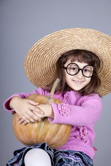 Funny Girl In Cap And Glasses Keeping Pumpkin. Royalty Free Stock Image