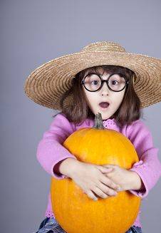 Funny Girl In Cap And Glasses Keeping Pumpkin. Royalty Free Stock Photos