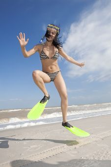 Girl In Swimming Mask And Fins Jumping At A Beach Royalty Free Stock Photo
