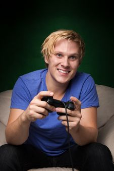 Free Smiling Young Man Playing Video Games Stock Photography - 16763382