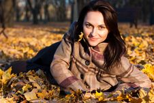 Beautiful Young Woman Lying In Autumn Leaves Royalty Free Stock Photos
