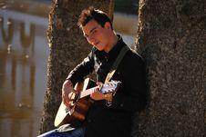 Free Man Playing Guitar Under Tree Stock Image - 16774851