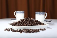 Display Of Roasted Coffee Beans With Two Cups Stock Photo