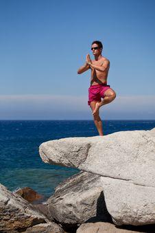 Man Meditating On A Rocky Beach Royalty Free Stock Photos