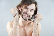 Free Guy Gnaws His Handcuffs Stock Photo - 16788200