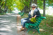Pretty Young Woman Resting On A Bench Stock Image