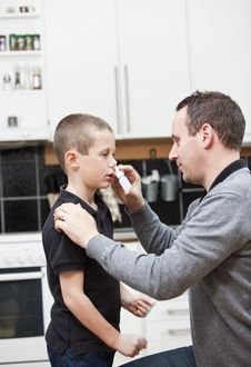 Free Father Giving Son Nose Drops Royalty Free Stock Images - 16823549