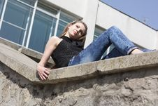Brunette Teenage Girl Sitting On The Wall