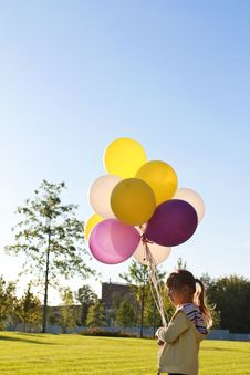 A Child With Multi-colored Balloons Royalty Free Stock Photography