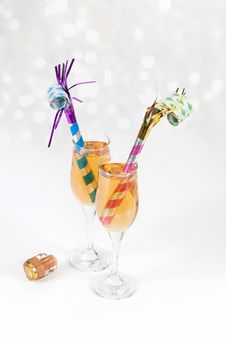 Noisemakers In Two Glasses Of Champagne With Cork Royalty Free Stock Photography