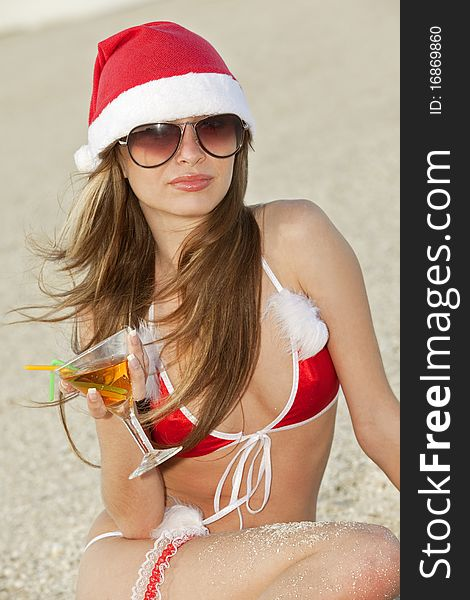 Woman in christmas suit with martini on the beach
