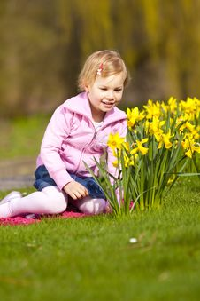 Little Girl And Daffodils In Park. Stock Images