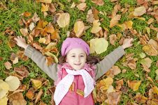 Little Girl At Grass And Leafs In The Park. Stock Photo
