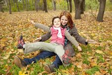 Free Two Sisters Sitting On The Leafs In The Park. Royalty Free Stock Photos - 16883448