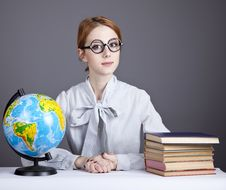 Free The Young Teacher In Glasses With Books And Globe Stock Photos - 16883923